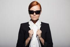 Το πορτρέτο μόδας της σοβαρής γυναίκας έντυσε ως μυστικός πράκτορας στοκ φωτογραφίες
