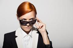 Το πορτρέτο μόδας της σοβαρής γυναίκας έντυσε ως μυστικός πράκτορας στοκ φωτογραφία