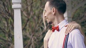 Το πορτρέτο, νέο όμορφο ζεύγος newlyweds που αγκαλιάζει, η νύφη ισιώνει τον κόκκινο δεσμό τόξων στο fiance της εξέταση κάθε έναν απόθεμα βίντεο