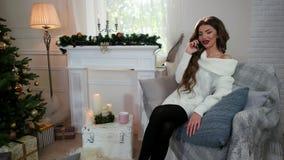 Το πορτρέτο, ομιλία κοριτσιών σε ένα κινητό τηλέφωνο καθμένος στον καναπέ, γυναίκα που φορά ένα θερμό πλεκτό πουλόβερ, χαλαρώνει  φιλμ μικρού μήκους