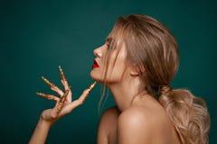 Το πορτρέτο ομορφιάς της αρκετά προκλητικής γυναίκας με τα κόκκινα χείλια, τα κόκκινα και χρυσά καρφιά, καρφώνει τη διακόσμηση, κ στοκ εικόνες