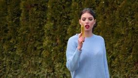 Το πορτρέτο που η ελκυστική νέα γυναίκα στη μπλε ζακέτα βγάζει την μπανάνα όπως το πυροβόλο όπλο, το κατευθύνει κατ' ευθείαν στη  απόθεμα βίντεο