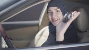 Το πορτρέτο της ανεξάρτητης συνεδρίασης γυναικών χαμόγελου νέας μουσουλμανικής στο αυτοκίνητο και το κυματίζοντας αυτοκίνητο κλει απόθεμα βίντεο