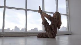 Το πορτρέτο της ανοιχτόχρωμης επιδερμίδας γυναίκας γιόγκας στον ερωδιό άσκησης στούντιο θέτει απόθεμα βίντεο