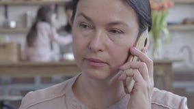 Το πορτρέτο της ανώτερης ομιλίας γυναικών στο κινητό τηλέφωνο, στην πλάτη είναι το daugher και το παιχνίδι εγγονών της στον πίνακ φιλμ μικρού μήκους