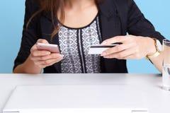 Το πορτρέτο της απρόσωπης γυναίκας φορά το μαύρο κοστούμι χρησιμοποιώντας το τηλέφωνο κυττάρων και την πιστωτική κάρτα καθμένος σ στοκ φωτογραφίες
