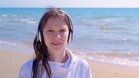 Το πορτρέτο της γυναίκας στα ακουστικά στο υπόβαθρο θάλασσας ακούει μουσική εξετάζει τη κάμερα φιλμ μικρού μήκους