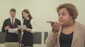 Το πορτρέτο της γυναίκας στην επίσημη ένδυση μιλά από το κινητό τηλέφωνο της στο πρώτο πλάνο στο γραφείο ενώ το αρσενικό και το θ απόθεμα βίντεο