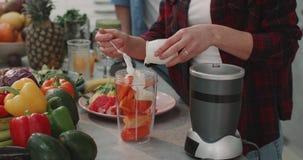Το πορτρέτο της γυναίκας στην κουζίνα προετοιμάζει έναν πορτοκαλή καταφερτζή από τα φρούτα και λαχανικά με το συνεργάτη της εκτός απόθεμα βίντεο