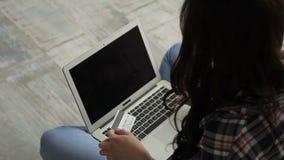 Το πορτρέτο της γυναίκας brunette που πληρώνει τους λογαριασμούς της με την πιστωτική κάρτα on-line απόθεμα βίντεο