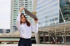 Το πορτρέτο της ελκυστικής επιχειρησιακής γυναίκας αυξάνει το φάκελλο εγγράφων γραφείων στην ασπίδα από το φως του ήλιου στοκ φωτογραφία με δικαίωμα ελεύθερης χρήσης