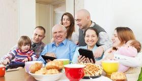 Η ευτυχής multigeneration οικογένεια χρησιμοποιεί τις ηλεκτρονικές συσκευές Στοκ Φωτογραφίες