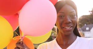 Το πορτρέτο της ελκυστικής γυναίκας χαμογελά και κρατά το μπαλόνι απόθεμα βίντεο