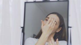Το πορτρέτο της νέας γυναίκας με το τέλειο δέρμα που εφαρμόζει μια κρέμα ημέρα-νύχτας στο πρόσωπό της φιλμ μικρού μήκους