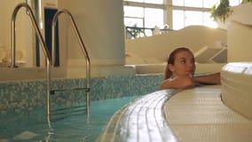 Το πορτρέτο της νέας γυναίκας που στέκεται στο εσωτερικό στην πισίνα κοντά στην παρυφή απόθεμα βίντεο