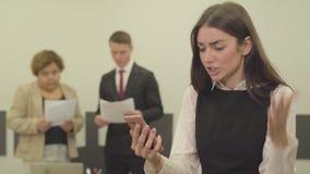 Το πορτρέτο της νέας γυναίκας στην επίσημη ένδυση μιλά από το κινητό τηλέφωνο της στο πρώτο πλάνο στο γραφείο ενώ το αρσενικόης τ φιλμ μικρού μήκους