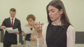 Το πορτρέτο της νέας γυναίκας στην επίσημη ένδυση μιλά από το κινητό τηλέφωνο της στο πρώτο πλάνο στο γραφείο ενώ το αρσενικόης τ απόθεμα βίντεο