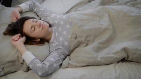 Το πορτρέτο της νέας γυναίκας brunette έντυσε στις γκρίζες πυτζάμες που βρίσκονται και που κοιμούνται στο κρεβάτι που καλύφθηκε μ απόθεμα βίντεο