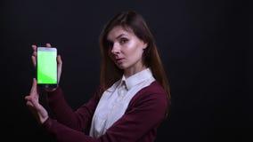 Το πορτρέτο της νέας επιχειρηματία brunette παρουσιάζει πράσινη οθόνη χρώματος του τηλεφώνου στη κάμερα στο μαύρο υπόβαθρο απόθεμα βίντεο