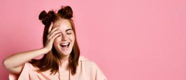 Το πορτρέτο της νέας ευτυχούς γυναίκας, που χαμογελά και που εξετάζει τη κάμερα, έκλεισε το μάτι με το χέρι στοκ εικόνα