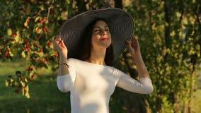Το πορτρέτο της νέας ευτυχούς όμορφης γυναίκας ευρύς-μέσα η τοποθέτηση καπέλων στο θερινό πάρκο απόθεμα βίντεο