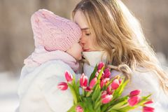 Το πορτρέτο της νέας μητέρας την φιλά λίγο μωρό το χειμώνα Στοκ Εικόνα