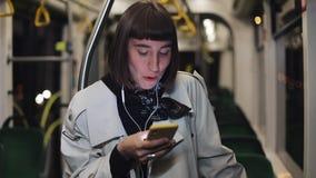 Το πορτρέτο της νέας μοντέρνης γυναίκας στα ακουστικά που ακούνε τη μουσική και που κοιτάζουν βιαστικά στο κινητό τηλέφωνο μεταφέ απόθεμα βίντεο