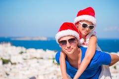 Το πορτρέτο της οικογένειας στα καπέλα Santa απολαμβάνει τις διακοπές Χριστουγέννων με την όμορφη άποψη Στοκ Εικόνες