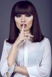 Το πορτρέτο της πανέμορφης νέας σκοτεινός-μαλλιαρής γυναίκας με προκλητικό κάνει τα επάνω και εκφραστικά μάτια ευθύ με τη χειρονο Στοκ Φωτογραφία