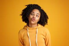 Το πορτρέτο της τρελλής νέας γυναίκας αφροαμερικάνων με το όμορφο χαμόγελο έντυσε στα περιστασιακά ενδύματα πέρα από το κίτρινο υ στοκ φωτογραφία με δικαίωμα ελεύθερης χρήσης