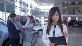 Το πορτρέτο της χαμογελώντας ασιατικής γυναίκας εμπόρων αυτοκινήτων στο ευτυχές νέο ζευγάρι υποβάθρου με το παιδί των ιδιοκτητών  απόθεμα βίντεο
