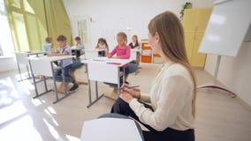 Το πορτρέτο της χαμογελώντας θηλυκής γυναίκας δασκάλων κατά τη διάρκεια του μαθήματος εκπαίδευσης με τους μαθητές στην τάξη στο δ απόθεμα βίντεο
