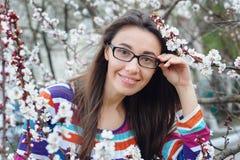 Το πορτρέτο της χαμογελώντας καυκάσιας γυναίκας brunette ανθίζει την άνοιξη κήπος Στοκ Εικόνα