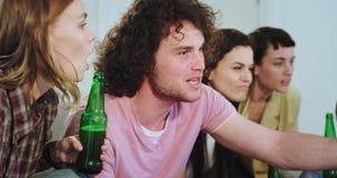 Το πορτρέτο της χαρισματικής νέας ομάδας φίλων μπροστά από τη TV υποστηρίζει την καλύτερη ομάδα ποδοσφαίρου τους πολύ συναισθηματ απόθεμα βίντεο