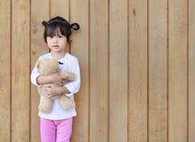Το πορτρέτο της χαριτωμένης στάσης μικρών κοριτσιών και το αγκάλιασμα Teddy αντέχουν ενάντια στον ξύλινο τοίχο σανίδων στοκ εικόνα με δικαίωμα ελεύθερης χρήσης