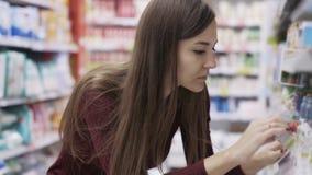 Το πορτρέτο της όμορφης γυναίκας με μακρυμάλλη παίρνει τα αγαθά από τα ράφια στην υπεραγορά απόθεμα βίντεο