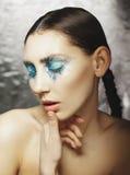 Το πορτρέτο της όμορφης γυναίκας με το μπλε αποτελεί στα μάτια και το μπλε Στοκ εικόνα με δικαίωμα ελεύθερης χρήσης