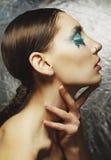Το πορτρέτο της όμορφης γυναίκας με το μπλε αποτελεί στα μάτια και το μπλε Στοκ Εικόνες