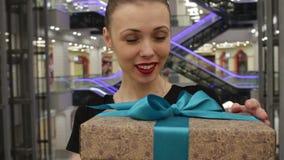Το πορτρέτο της όμορφης γυναίκας σε ένα μαύρο φόρεμα παίρνει ένα δώρο Εξετάζει τη κάμερα και το χαμόγελο φιλμ μικρού μήκους