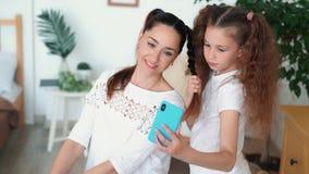Το πορτρέτο της όμορφης μητέρας και η κόρη της κάνουν selfie στο τηλέφωνο, σε αργή κίνηση φιλμ μικρού μήκους