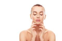 Το πορτρέτο της όμορφης νέας γυναίκας με το καθαρό, φρέσκο δέρμα αγγίζει το πρόσωπό της στο απομονωμένο άσπρο υπόβαθρο Στοκ φωτογραφία με δικαίωμα ελεύθερης χρήσης