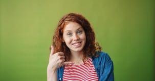 Το πορτρέτο της όμορφης παρουσίασης κοριτσιών με καλεί χειρονομία και χαμόγελο στο πράσινο υπόβαθρο απόθεμα βίντεο