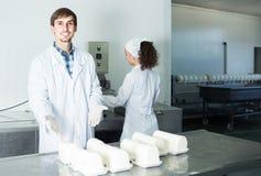 Το πορτρέτο του άνδρα και η γυναίκα που ντύνεται στα παλτά εργαστηρίων φαίνονται ευτυχή Στοκ Φωτογραφίες