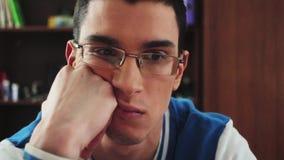 Το πορτρέτο του αγοριού στα γυαλιά σοβαρά κοιτάζει στην οθόνη Χέρι λαβής στο μάγουλο Σπουδαστής άντεξε Κοιτάξτε στο ρολόι φιλμ μικρού μήκους