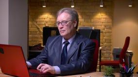 Το πορτρέτο του ανώτερου επιχειρηματία στην επίσημη δακτυλογράφηση κοστουμιών στο lap-top γυρίζει στη κάμερα και τα χαμόγελα στην φιλμ μικρού μήκους
