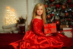 Το πορτρέτο του αρκετά ξανθού κοριτσιού φορά διακοσμημένη φορεμάτων μόδας το κόκκινο πλησίον χριστουγεννιάτικο δέντρο Στοκ Εικόνες
