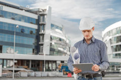 Το πορτρέτο του βέβαιου νέου αρχιτέκτονα ή του κύριου μηχανικού χρησιμοποιεί την ψηφιακή ταμπλέτα στο εργοτάξιο οικοδομής Στοκ φωτογραφία με δικαίωμα ελεύθερης χρήσης