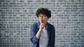 Το πορτρέτο του ελκυστικού κοριτσιού σχετικά με τα χείλια με το δάχτυλο είναι ήρεμο και κρατά μυστικός απόθεμα βίντεο