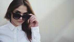 Το πορτρέτο του ελκυστικού νέου χαμόγελου γυναικών στην παραλία αφαιρεί τα γυαλιά ηλίου δροσερά απόθεμα βίντεο