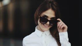 Το πορτρέτο του ελκυστικού νέου χαμόγελου γυναικών στην παραλία αφαιρεί τα γυαλιά ηλίου δροσερά φιλμ μικρού μήκους
